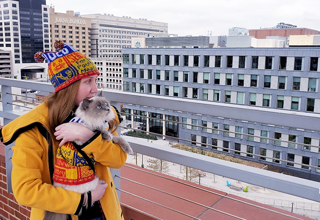 The author and her cat enjoy Baltimore views while wearing matching knit apparel.