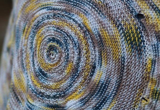 A close up of the detailed knitwork in the yellow and blue shawl.