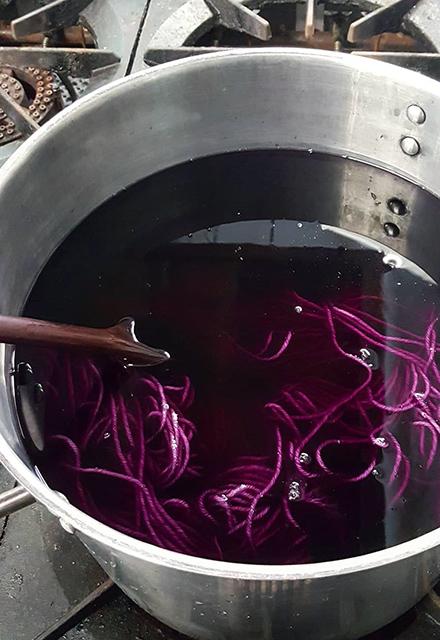 Wool in a vat of deep purple dye.