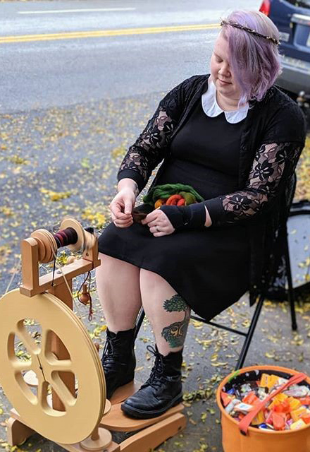 A woman spins yarn while seated.