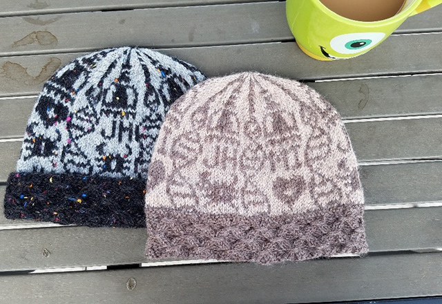 Two knit hats lay on a wooden table.