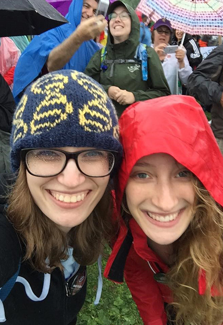 Two students pose together, one wearing a knit hat.