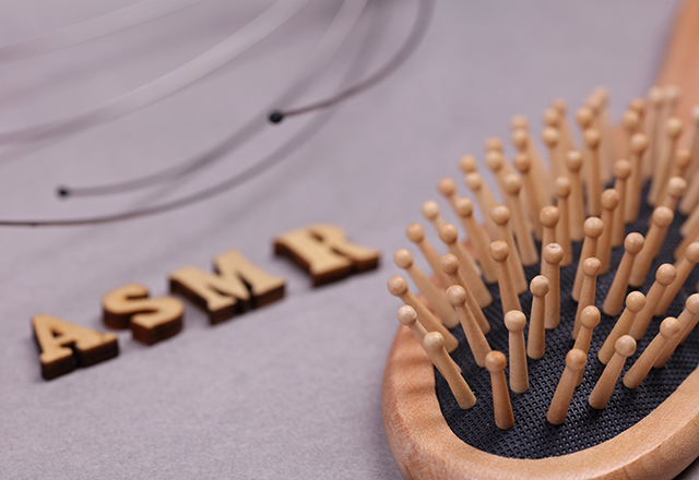 "A hairbrush lies in the foreground; behind it are wooden letters spelling ""ASMR."""