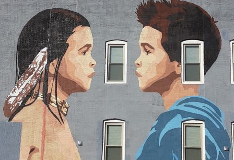 A mural of a Native American boy and a caucasian boy facing one another.