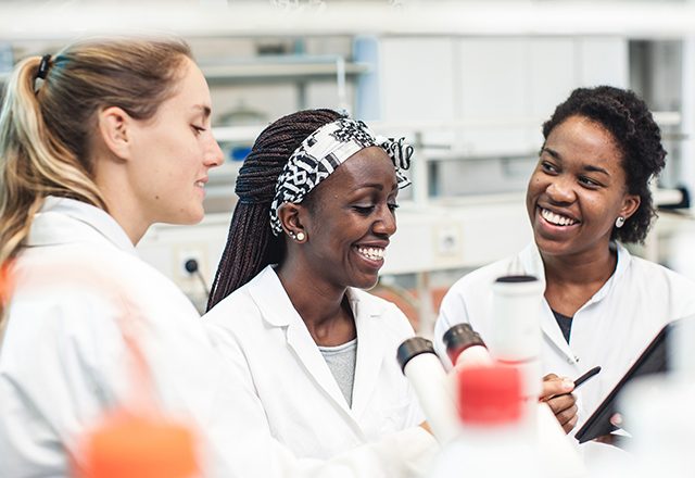 A diverse group of female scientists work together in the lab.