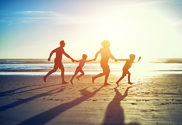 A carefree family of four enjoy a run on the beach, with the sun behind them.