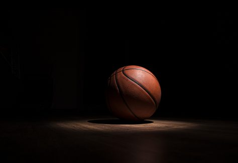 A basketball sits alone in a spotlight.