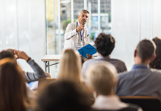 Male doctor talking to large group of people during a seminar in a board room.