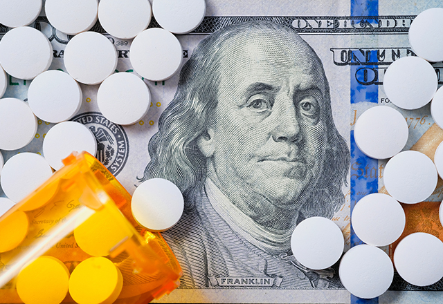 White prescription pills spilled across an American hundred dollar bill.