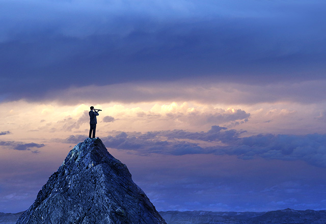 A silhouetted businessman stands on top of a mountain peak and looks into the distance with a spyglass in front of a dramatic sunset in the distance.
