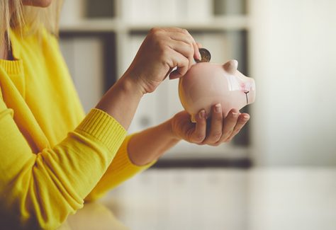A woman inserts a coin into a piggy bank.