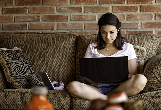 A young woman sits on the couch, using her laptop.