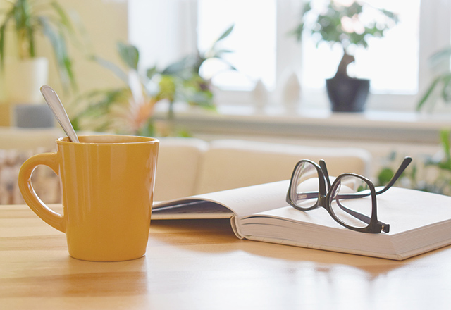 Yellow cup of tea, book and glasses on the table, cozy home interior background