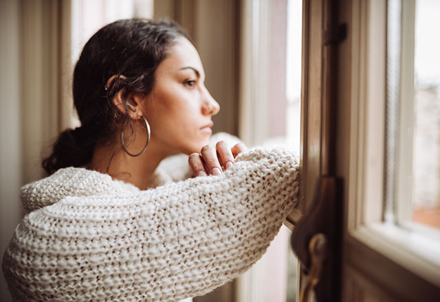 A pensive woman looks out of a window.