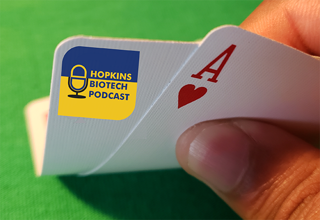 A close up of a pair of playing cards, one of which has the Hopkins Biotech Podcast logo.