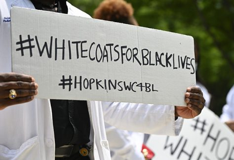 "A Black member of Hopkins staff holds a sign that says, ""White Coats for Black Lives."""