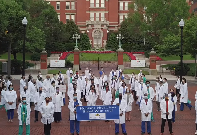 "a group of Johns Hopkins doctors holding a sign that says "" we stand with you""."