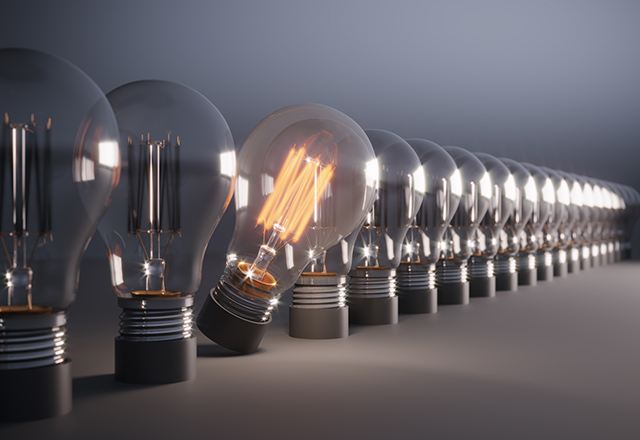 A glowing lightbulb stands out in a lineup of darkened bulbs.