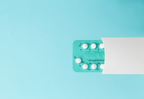 Pack of oral contraceptive pills on a blue background.