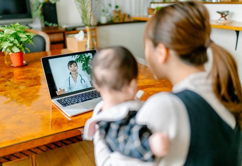 A mother with her baby is video calling a doctor on a laptop from home.