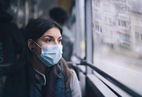 Young woman wearing protective face mask, sitting in bus transportation in the city.