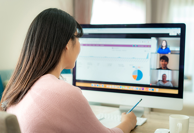 A woman sits at her desk, talking to her classmates using video conference software.