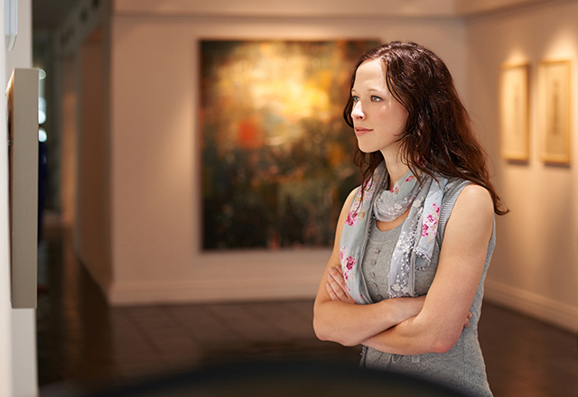 Shot of a young woman looking at paintings in a gallery