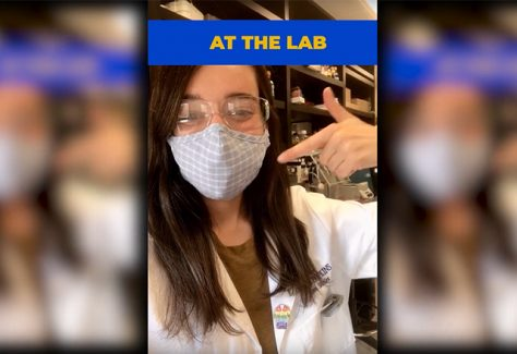 A Hopkins student points to her mask while in the lab.