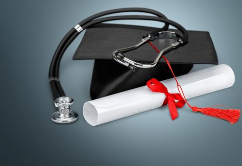 A graduation cap with a diploma and stethoscope.