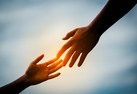 Two hands reach to connect with one another.