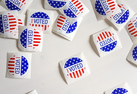"""A collection of """"I Voted"""" stickers scattered across a table."""
