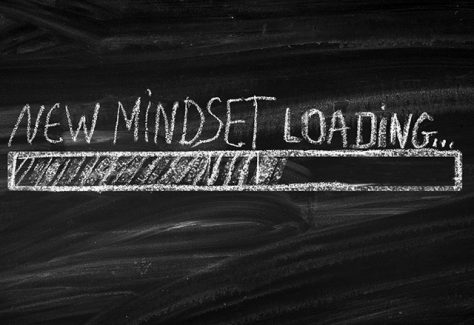 "A chalkboard with ""New Mindset Loading"" written in white chalk."