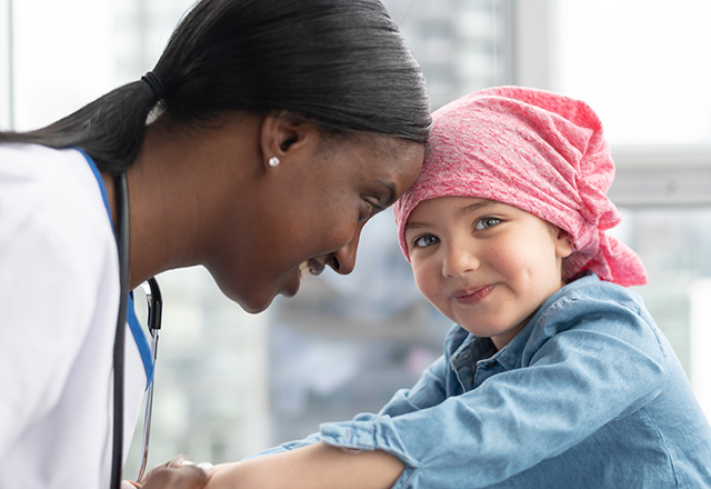 A cute elementary age girl with cancer is wearing a pink scarf on her head. She is at a medical appointment. The female doctor of African descent is holding the child's hands, providing comfort and support. The child is smiling at the camera.