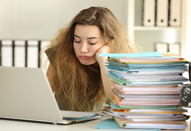 Exhausted young woman with tousled hair working hard reading a lot of documents at office.