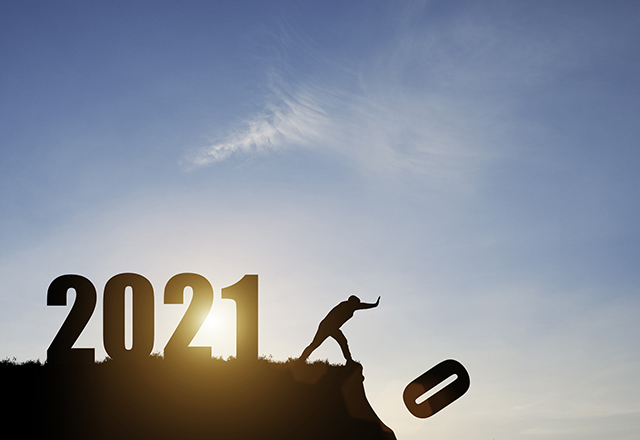A man pushes the number zero off of a cliff; behind him is the number 2021 with a blue sky and sunrise.