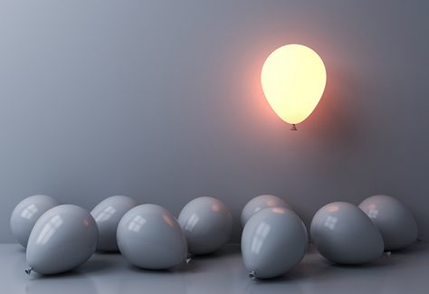 One balloon glows as it floats above other white balloons scattered along the floor in shadow.
