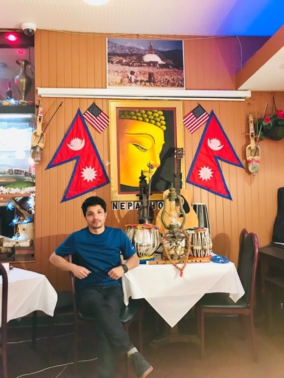 Surya sits at a table; there are traditional Nepalese instruments on the table. On the walls are posters and flags of Nepal.