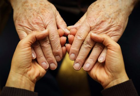 A pair of young hands hold a pair of older hands in a gesture of support.