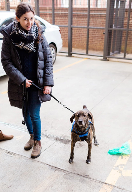 Carli Jones stands outside, smiling, with a sweet-looking medium-sized dog on a leash.