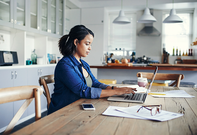 Shot of a young woman using a laptop while working from home.