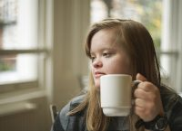 Portrait of girl with down syndrome having breakfast.