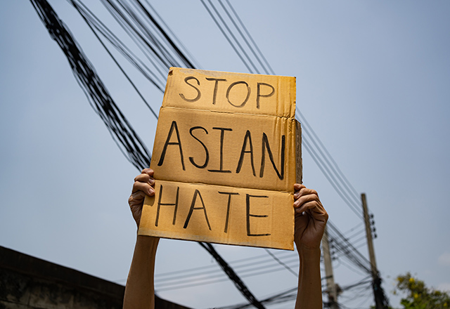 "Two arms holding up a handmade sign that says ""Stop Asian Hate."""