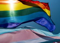 closeup of a gay pride flag and a transgender pride flag waving on the blue sky, moved by the wind, with the sun in the background