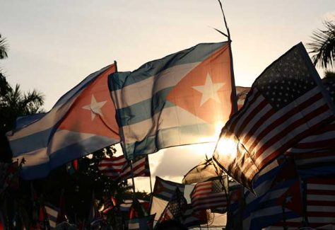 Cuban and American flags with a sunset in the distance