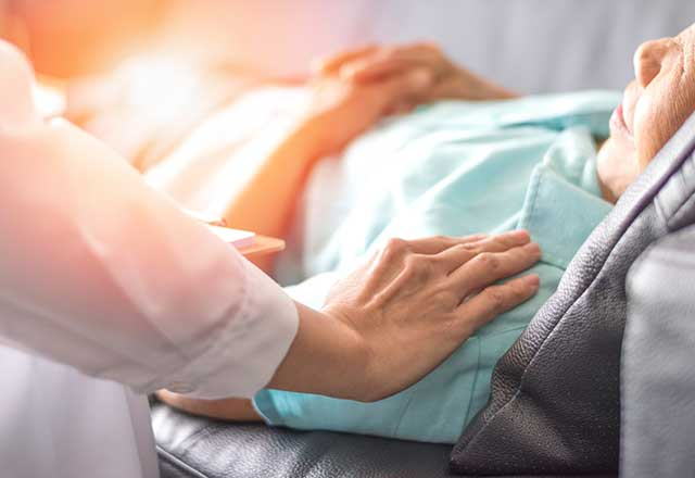 A healthcare worker comforting a patient lying in a hospital bed.