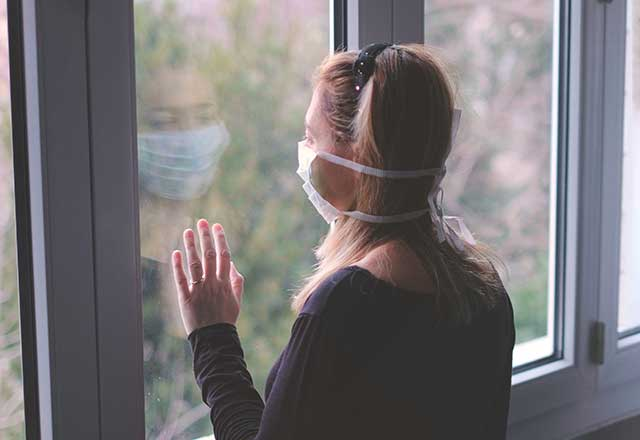 Masked women looking out a window