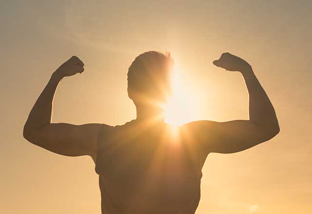 Person flexing silhouetted by the sun in the background