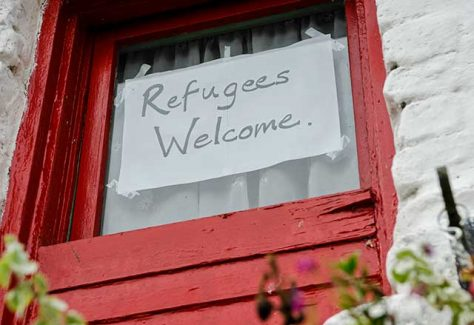 Refugees welcome sign on a door.